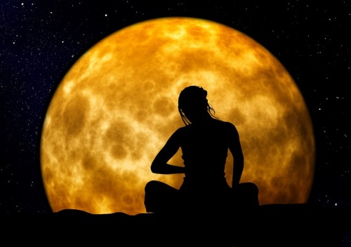 woman sitting in front of moon
