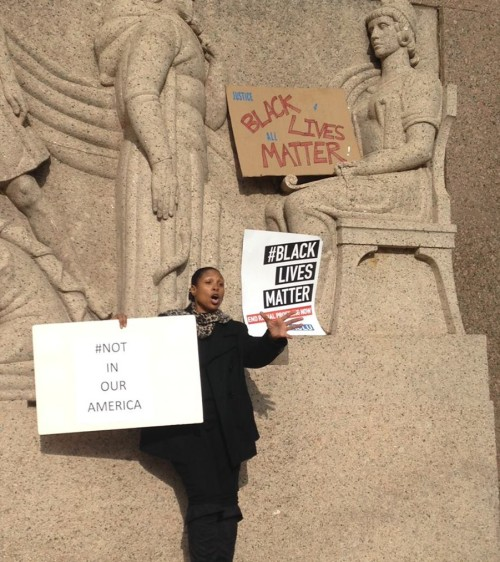 woman standing in front of bas relief sculptures with protest signs