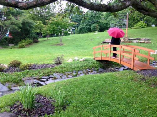 Mom walks across the Peace Park bridge with her red umbrella.