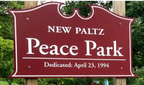 Red and white sign reads: New Paltz Peace Park. Dedicated: April 23, 1994
