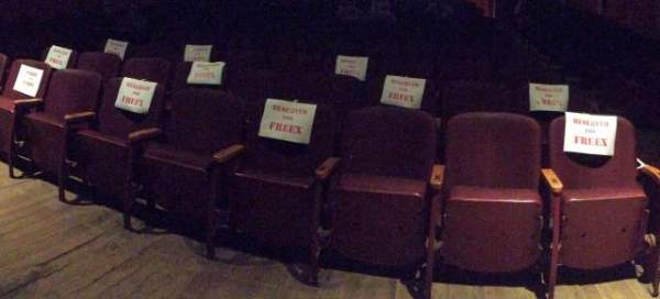 Red Rosendale Theatre seats with signs taped to them: