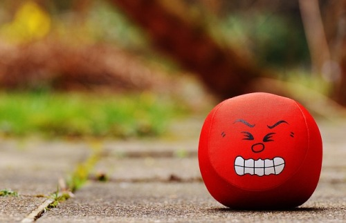Angry red stress ball sitting on a sidewalk