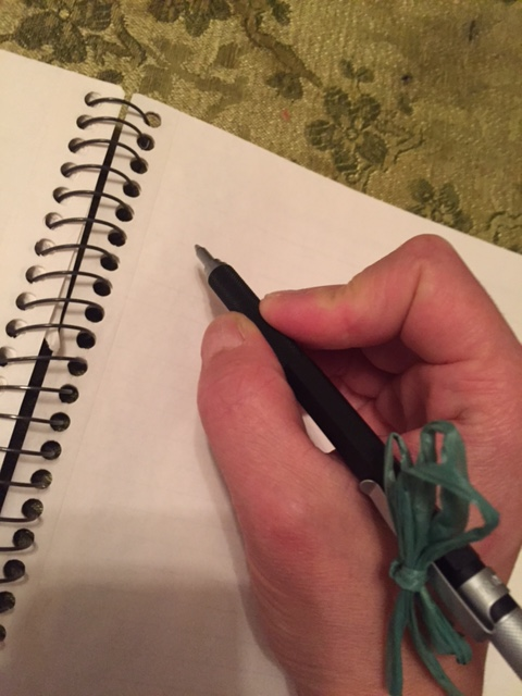 A hand holds a pen with ribbon tied to it over a notebook